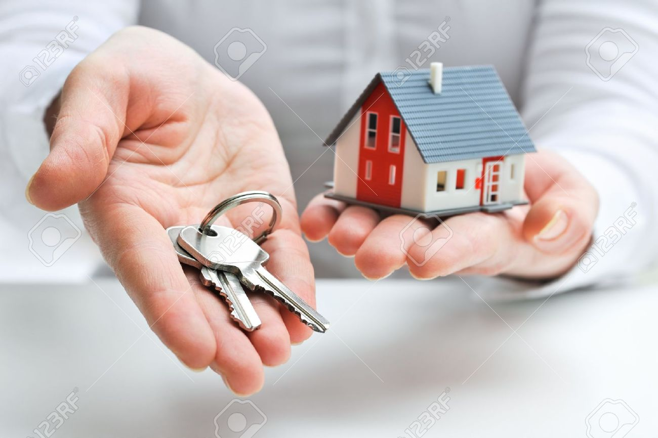 18148501-Agente-immobiliare-con-il-modello-di-casa-e-le-chiavi-Archivio-Fotografico
