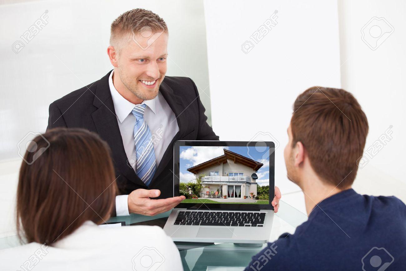 28161926-Sorridere-consulente-mostrando-casa-foto-per-coppia-sul-computer-portatile-alla-scrivania-in-ufficio-Archivio-Fotografico