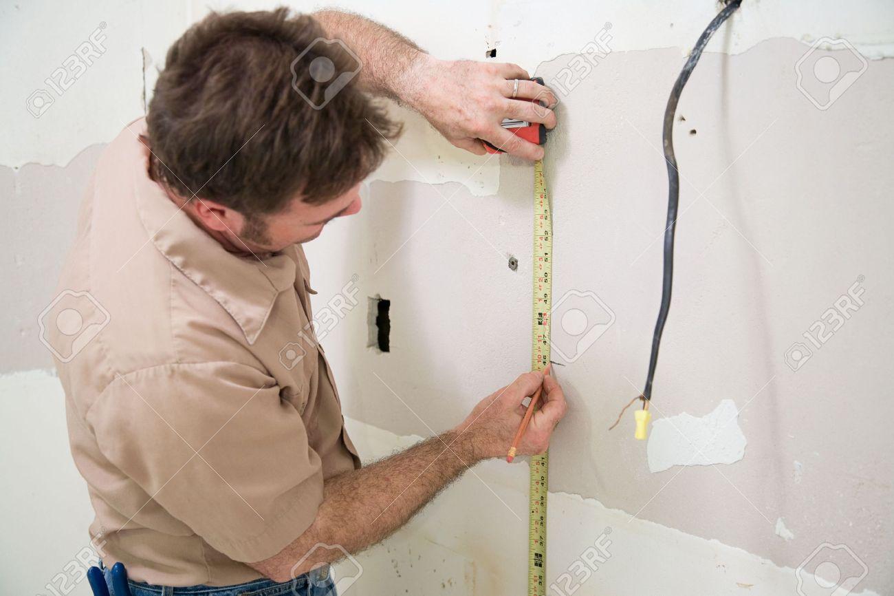3451643-Contraente-di-misura-e-la-marcatura-drywall-dove-vuole-tagliare-fuori-l-apertura-di-una-casella-di-a-Archivio-Fotografico